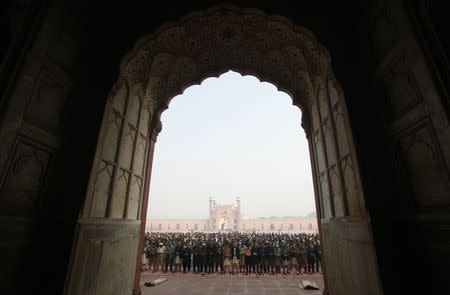 People hold funeral prayers for the victims of the Taliban attack on the Army Public School in Peshawar, at the Badshahi Mosque in Lahore