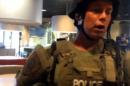 This image taken from video provided by Wesley Lowery of The Washington Post shows a police officer confronting Lowery in a fast-food restaurant in Ferguson, Mo., on Wednesday Aug. 13, 2014. Lowery of The Washington Post, and Ryan Reilly of The Huffington Post, said they were handcuffed and put into a police van after officers came in to quickly clear the fast-food restaurant where they were doing work while covering the protests in the town. (AP Photo/The Washington Post, Wesley Lowery) MANDATORY CREDIT TO WASHINGTON POST AND WESLEY LOWERY.