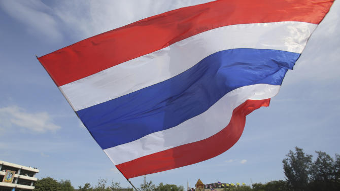 An anti-government protester waves a Thai national flag at the Royal Thai Army compound compound in Bangkok, Thailand, Friday, Nov. 29, 2013. The protesters stormed into the national army headquarters on Friday, breaking into their latest high-profile target in a bid to topple Prime Minister Yingluck Shinawatra. (AP Photo/Sakchai Lalit)