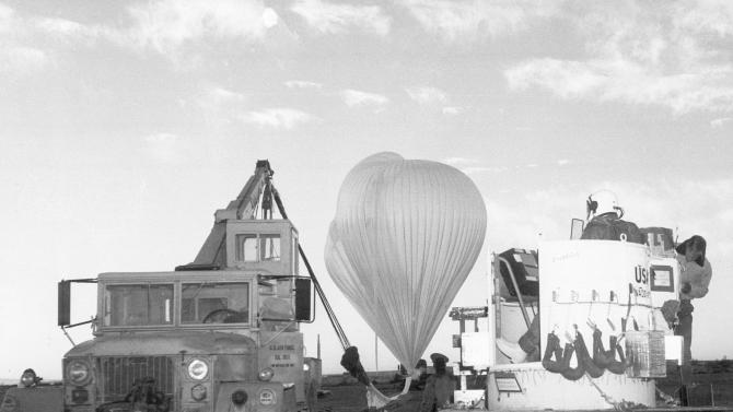 FILE- In this Nov. 16, 1959, file photo, provided by the U.S. Air Force, Capt. Joseph Kittinger Jr. waits in the open balloon gondola, right, while the two million cubic-foot polyethylene balloons are filled with helium for the Excelsior I test jump at White Sands Missile Range, N.M. Kittinger made the first free-fall parachute jump at an altitude of 76,400 feet, setting a record. On Tuesday, Oct. 9, 2012, if winds allow, in the desert surrounding Roswell, N.M., pilot Felix Baumgartner will attempt to break Kittinger's world record for the highest and fastest free fall. (AP Photo/U.S. Air Force, File)