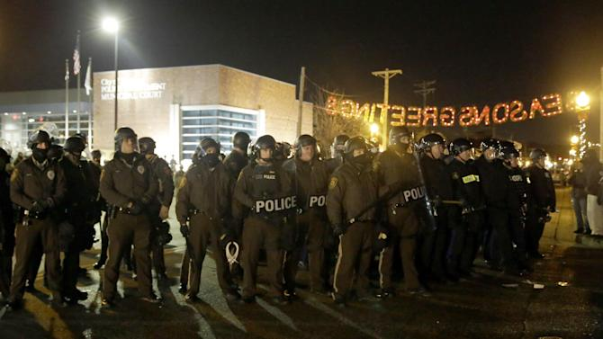 Police stand guard as protesters gather in front of Ferguson Police Department on Friday, Nov. 28, 2014, in Ferguson, Mo. Several protesters have been taken into custody during a demonstration outside the police department. Tensions escalated late Friday during an initially calm demonstration after police said protesters were illegally blocking West Florissant Avenue. (AP Photo/Jeff Roberson)