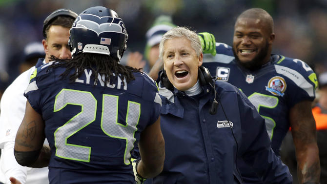 Seattle Seahawks head coach Pete Carroll congratulates running back Marshawn Lynch (24) after Lynch scored on a 20-yard touchdown run during the first quarter of an NFL football game against the Arizona Cardinals in Seattle, Sunday, Dec. 9, 2012. (AP Photo/John Froschauer)