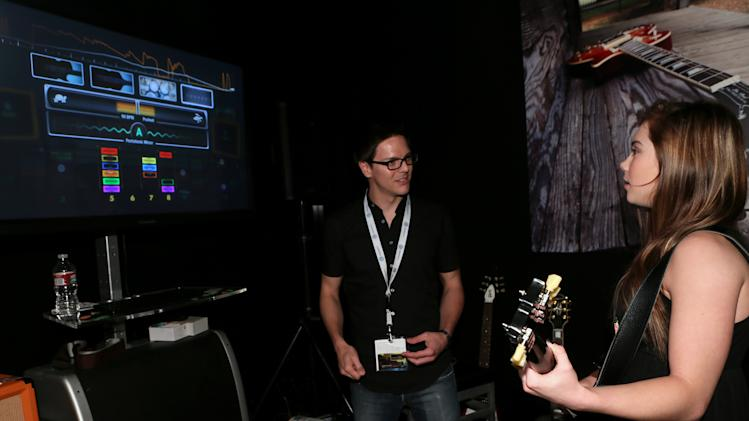 "McKayla Maroney, right, plays ""Rocksmith 2014"" at the Ubisoft booth at E3 on Wednesday, June 12, 2013, in Los Angeles. (Photo by Alexandra Wyman/Invision for Ubisoft/AP Images)"