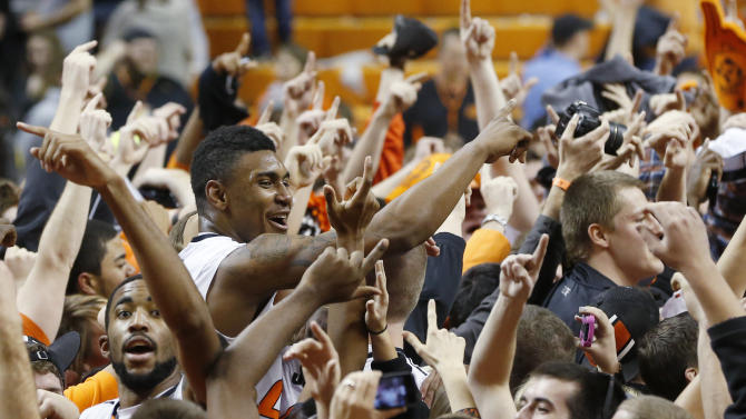 Oklahoma State forward Michael Cobbins, left, and guard Le'Bryan Nash, second from left, celebrate with fans following an 84-79 victory over Oklahoma in an NCAA college basketball game in Stillwater, Okla., Saturday, Feb. 16, 2013. (AP Photo/Sue Ogrocki)