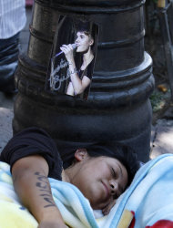 A girl sleeps under a picture of Justin Bieber near Mexico City's main historic plaza, the Zocalo, Sunday, June 10, 2012. The Beliebers have arrived in the chaotic streets of Mexico City, adolescents in purple and white and braving two nights on roach-infested sidewalks for a chance to be closest to the stage when teenage superstar Justin Bieber puts on a free concert Monday evening on the capital's vast central plaza.(AP Photo/Marco Ugarte)