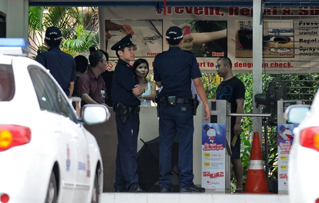 Policemen stand by the entrance to a foreign workers dormitory in Singapore on November 26, 2012. More than 100 mainland Chinese bus drivers in Singapore refused to work in a rare case of labour mass action in the city-state. AFP PHOTO/ROSLAN RAHMAN