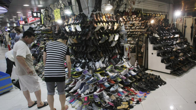 South Koreans at shoes at a store in Seoul, South Korea, Wednesday, July 27, 2011. South Korea's economic growth slowed in the second quarter as weaker exports, manufacturing and services offset stronger consumer spending and rebounds in capital outlays and construction, the central bank said Wednesday.(AP Photo/Ahn Young-joon)