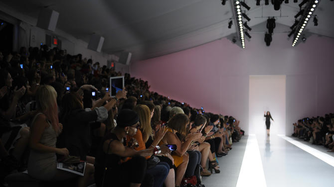 Camera phones and ipads are illuminated as designer Jill Stuart  waves to the audience after her Spring 2013 collection was modeled during Fashion Week in New York, Saturday Sept 8, 2012. (AP Photo/Stephen Chernin)