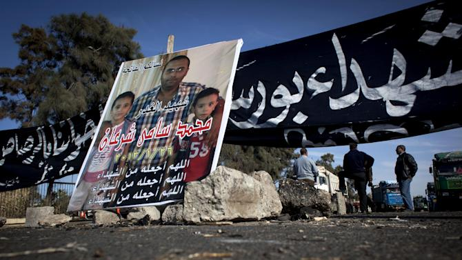 """Egyptian protesters block the road leading to the east port preventing loaded trucks from leaving the port, during the fifth day of a general strike, in Port Said, Egypt, Thursday, Feb. 21, 2013. A banner with Arabic that reads """"retribution for Port Said martyrs, they shot our brothers with bullets,"""" and a poster with a picture of a slain man with his kids and reading in Arabic """"the martyr of treachery, Mohammed Sami Sharan, may God count him as a martyr, January 26, 2013,"""" are used to block the road. (AP Photo/Nasser Nasser)"""