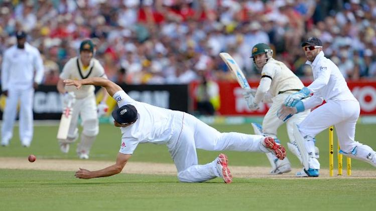 England captain Alastair Cook (C) dives to stop the ball from Australian batsman Michael Clarke on the first day of the second Ashes Test cricket match in Adelaide on December 5, 2013