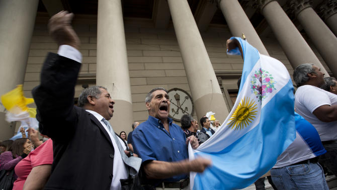 Faithful wave an Argentine flag and sing outside the Metropolitan Cathedral as they celebrate in Buenos Aires, Argentina, Wednesday, March 13, 2013.  Latin Americans reacted with joy on Wednesday at news that Bergoglio was elected pope. Bergoglio, who chose the name Pope Francis, is the first pope ever from the Americas.  (AP Photo/Victor R. Caivano)