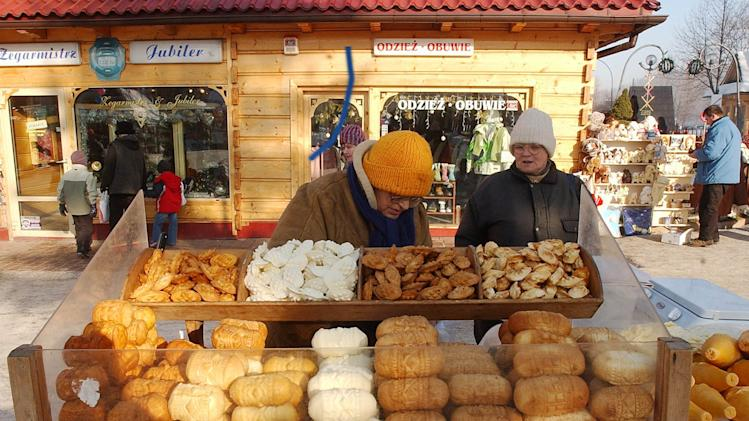 FILE - This is a  Jan. 14, 2006 file photo of a street vendor selling regional smoked cheese 'oscypek '  in Zakopane, Poland. Little Miss Muffet could have been separating her curds and whey from the sixth millennium B.C., according to a new study that finds the earliest solid evidence of cheese-making. Scientists performed a chemical analysis on fragments from 34 pottery sieves discovered in Poland to determine what they were used for. Until now, experts weren't sure whether such sieves were used to make cheese, beer or honey. (AP Photo/Czarek Sokolowski, File)