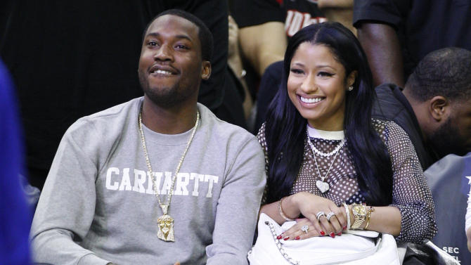 FILE - In this Jan. 16, 2016 file photo, Nicki Minaj, right, and Meek Mill, left, watch action from the sidelines during the first half of an NBA basketball game between the Portland Trail Blazers and the Philadelphia 76ers, in Philadelphia. Mill must serve three months of house arrest for parole violations that he blames on his erratic concert schedule but Philadelphia prosecutors link to his romance with Minaj. Common Pleas Judge Genece Brinkley also ordered him to spend six more years on probation.(AP Photo/Chris Szagola, File)