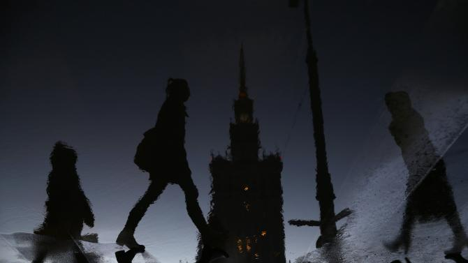 Women are reflected in a puddle as they walk in front of the Palace of Culture during rainy day in Warsaw