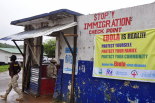 CLICK IMAGE for slideshow: A Liberian soldier, left, mans a checkpoint to control the movement of people as authorities try to prevent the Ebola virus...