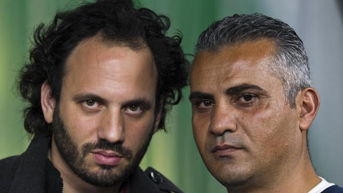"""In this Tuesday, Feb. 5, 2013 photo, documentary film Co-directors, Israeli, Guy Davidi, left, and Palestinian, Emad Burnat, pose for a photo after an interview in Los Angeles. Their 2011 documentary film, """"5 Broken Cameras,"""" is nominated for an Oscar in the best Documentary Feature category.  (AP Photo/Damian Dovarganes)"""