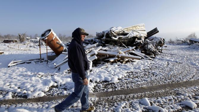 Leon Gilbert walks by a damaged house covered in snow following a tornado several days earlier in Marysville, Ind., Monday, March 5, 2012. According to utility company Clark County REMC, nearly 8,000 of its service members in Indiana were without service after the tornadoes. (AP Photo/Nam Y. Huh)