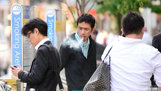 People are seen at a designated smoking area on a street in Tokyo, on May 31, 2013