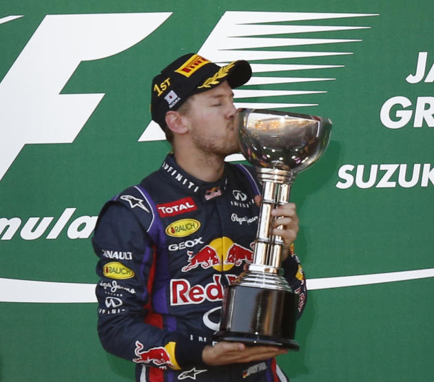 Red Bull Formula One driver Vettel of Germany kisses his trophy after winning the Japanese F1 Grand Prix at the Suzuka circuit