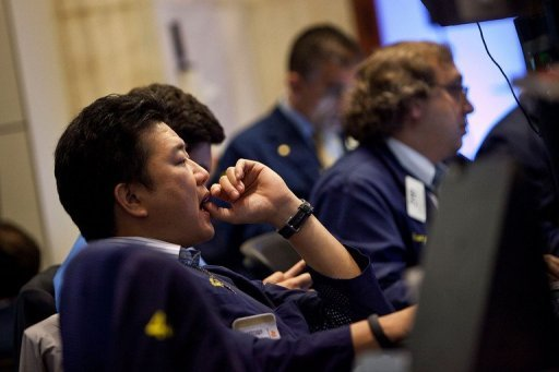 <p>A trader works on the floor of the New York Stock Exchange on October 19. A diminished sales forecast by industrial bellwether Caterpillar clouded stocks Monday, but a last-minute burst of buying pushed the Dow and S&P 500 barely back into the black for the session.</p>