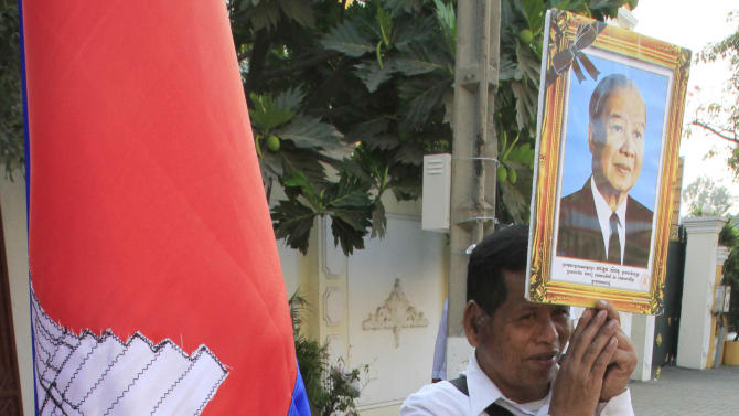 A mourner prays for the late former King Norodom Sihanouk beside the national flag in Phnom Penh Saturday, Feb. 2, 2013.  Sihanouk's body had been lying in state at the Royal Palace after being flown from Beijing where he died Oct. 15 of a heart attack at the age of 89. The cremation, the climax of seven days of mourning, will take place Monday. (AP Photo/Heng Sinith)