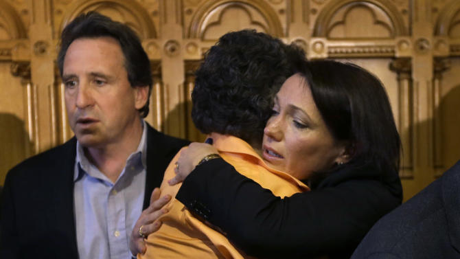 Nicole Hockley, right, mother of Sandy Hook School shooting victim Dylan Hockley, hugs Conn. state Sen. Beth Bye, D-West Hartford, center, as Neil Heslin, behind left, father of Sandy Hook shooting victim Jesse Lewis, looks on at the conclusion of legislation signing ceremonies at the Capitol in Hartford, Conn., Thursday, April 4, 2013. The legislation signed by Malloy adds more than 100 firearms to the state's assault weapons ban, sets eligibility rules for buying ammunition, and creates what officials have called the nation's first dangerous weapon offender registry. (AP Photo/Steven Senne)