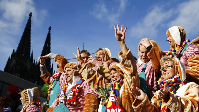"Carnival revellers on a float pass the Cologne cathedral as they take part in the ""Rosenmontag"" (Rose Monday) parade"