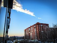 The trail of a falling object is seen above a residential apartment block in Chelyabinsk, Russia, on February 15, 2013. Morning traffic ground to a sudden halt in the city as a falling meteor partially burned up in the lower atmosphere above the city and lit up the morning sky