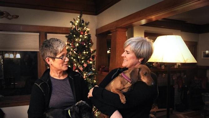 "Former Army Major Margaret Witt, right, and Lori Johnson, left, stand in their south hill home, Monday, Dec. 3, 2012 in Spokane, Wash. They are planning to marry in a few weeks after receiving one of the first marriage licenses for same sex couples this week. Witt fought the Army over ""Don't Ask, Don't Tell"" and was with President Obama when he signed the repeal.  (AP Photo/The Spokesman-Review, Jesse Tinsley)  COEUR D'ALENE PRESS OUT   MBI"