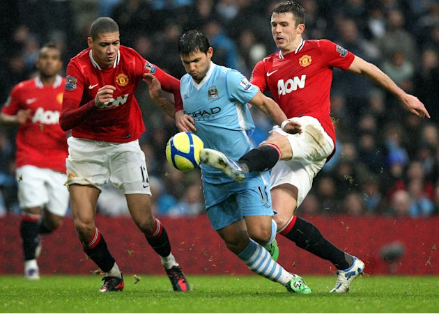 Manchester City's Sergio Aguero, center, vies for the ball with Manchester United's Chris Smalling, left, and Michael Carrick during their English FA Cup third round soccer match at the Etihad stadium