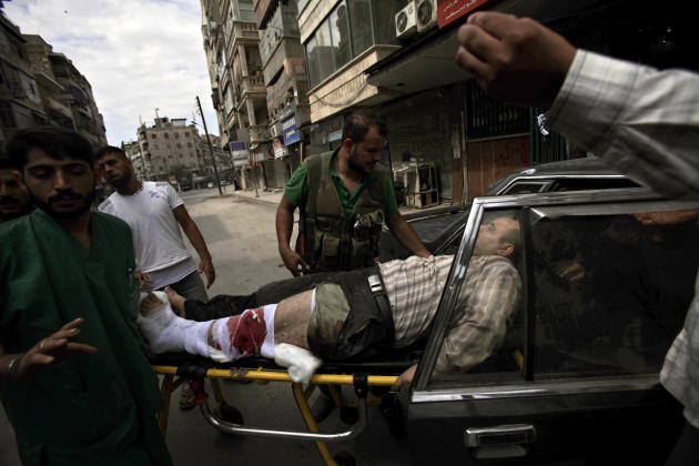 Syrian rebels and medical staff put an injured man into a car after being shot by government forces, outside a hospital in Aleppo, Syria, Tuesday, Sept. 11, 2012. (AP Photo/Muhammed Muheisen)