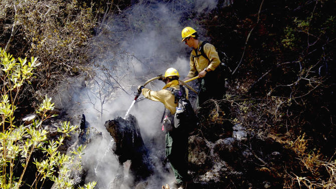 Firefighters work on extinguishing a fire in the Los Padres National Forrest near Santa Barbara, Calif. on Tuesday, May 28, 2013. Firefighters took advantage of a lull in winds on Tuesday to try to gain ground against a forest fire in mountains north of Santa Barbara, as crews elsewhere in Southern California chased a new fire north of Los Angeles and sought to increase containment of a rural San Diego County blaze. (AP Photo/Nick Ut)