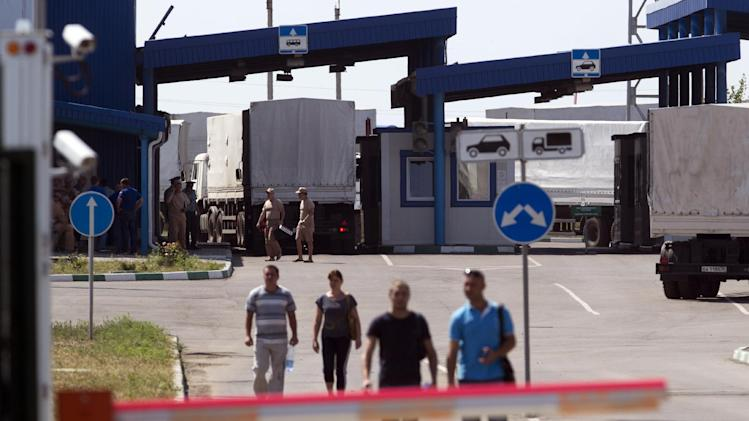 Trucks of the Russian aid convoy are searched at a Russian inspection zone inside a border control point with Ukraine in the Russian town of Donetsk, Rostov-on-Don region, Russia, Friday, Aug. 22, 2014. The first trucks of the Russian aid convoy crossed the Ukrainian inspection zone Friday morning. (AP Photo/Pavel Golovkin)