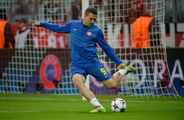 Arsenal's striker Lukas Podolski warms-up prior to a UEFA Champions League last 16 second-leg football match against Bayern Munich in Munich, southern Germany, on March 11, 2014