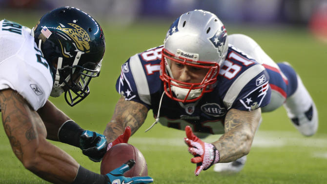 New England Patriots tight end Aaron Hernandez (81) fumbles as Jacksonville Jaguars safety Dawan Landry (26) recovers the ball during the first quarter of their NFL preseason football game in Foxborough, Mass., Thursday night, Aug. 11, 2011. (AP Photo/Michael Dwyer)