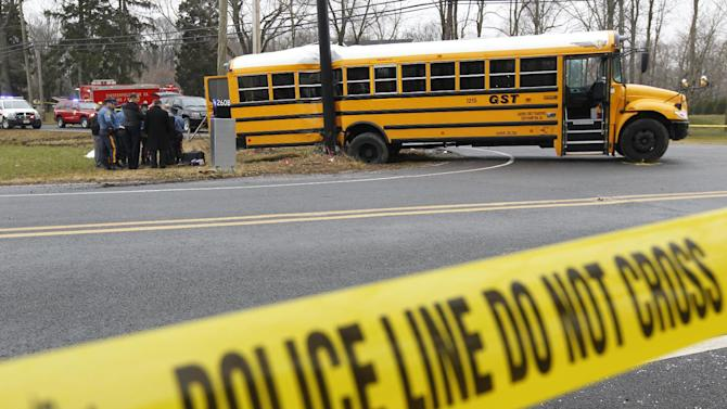 FILE - This Feb. 16, 2012 file photo shows investigators viewing the scene of a school bus crash in Chesterfield, N.J. Federal investigators are expected to make new school bus safety recommendations based on fatal accidents in New Jersey and Florida last year. The National Transportation Safety Board (NTSB) meets Tuesday to consider a report on the probable cause of an accident in Chesterfield, N.J., in which a dump truck slammed into the back left side of a school bus, spinning the bus around until it collided with a traffic signal pole. An 11-year-old girl was killed and five other students — including the girl's two sisters — were seriously injured. (AP Photo/Matt Rourke, File)