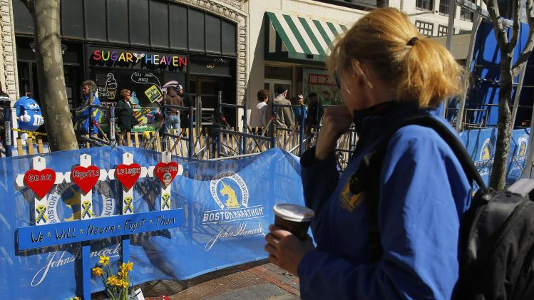 A woman pauses in front of a memorial for the victims of the 2013 Boston Marathon bombings at the site of the first bomb blast in Boston