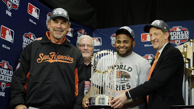San Francisco Giants owner Bill Neukom, right to left, Pablo Sandoval, Brian Sabean and Bruce Bochy holds the Commissioner's Trophy after Game 4 of baseball's World Series against the Detroit Tigers Sunday, Oct. 28, 2012, in Detroit. The Giants won 4-3 to win the series. (AP Photo/Matt Slocum, Pool )