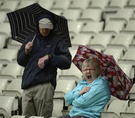 Spectators with umbrellas wait as rain falls during the third one-day international between England and Australia at Edgbaston cricket ground in Birmingham