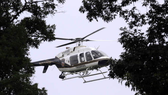 A Pennsylvania State Police helicopter flies above Renninger Road in Douglass Township during the investigation of a fatal shooting Sunday July 3, 2011. A shooting at a rural home in suburban Philadelphia killed two people, including a child, and injured three others, authorities said Sunday. A manhunt is under way for the shooter.  (AP Photo/Jacqueline Larma)
