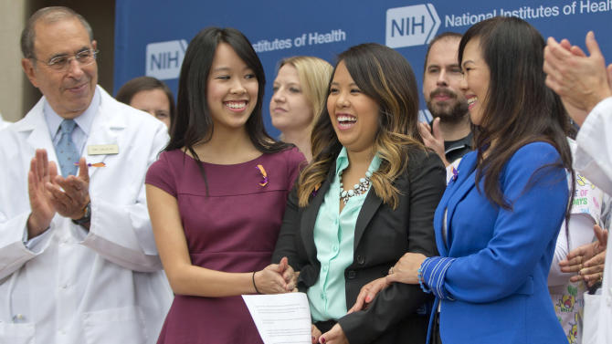 Patient Nina Pham, center, with her mother Diana Berry, right, and sister Cathy Pham, left, smiles as members of the NIH staff outside applaud during a news conference at NIH in Bethesda, Md., Friday, Oct. 24, 2014. Pham, the first nurse diagnosed with Ebola after treating an infected man at a Dallas hospital is free of the virus. The 26-year-old Pham arrived last week at the NIH Clinical Center. She had been flown there from Texas Health Presbyterian Hospital Dallas. (AP Photo/Pablo Martinez Monsivais)
