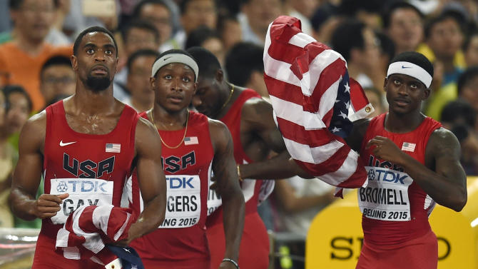 US team folds up their national flags after learning of their disqualification in the men's 4 x 100 metres relay final at the 15th IAAF Championships in Beijing