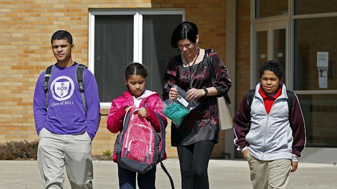 FILE - In this March 16, 2011 file photo, Heather Coffy, right center, leaves the St. Monica School with her children, left to right, Delano Coffy, 15, Alanna Marshall, 8, and Darius Coffy, 11, in Indianapolis. Students like Delano are at the heart of brewing political fights and court battles over whether public dollars should go to school vouchers to help make private schools more affordable. (AP Photo/Michael Conroy, File)