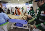 A victim is carried on a stretcher at Red Cross Hospital in Ishinomaki, Miyagi Prefecture, Sunday, March 13, 2011, two days after a powerful earthquake-triggered tsunami hit the country's east coast.