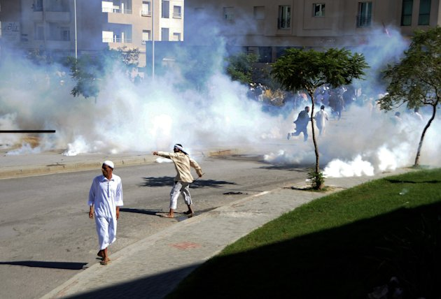 Demonstrators throw stones during a protest against the anti-Islam film &quot;Innocence of Muslims&quot; outside the U.S. Embassy in Tunis, Tunisia, as police respond with tear gas Friday, Sept. 14, 2012. Protests against he film spread to their widest extent yet around the Middle East and other Muslim countries Friday, as protesters smashed into the German Embassy in the Sudanese capital and security forces in Egypt and Yemen fired tear gas and clashed with protesters to keep them away from U.S. embassies. (AP Photo/Hassene Dridi)
