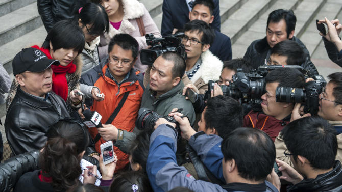 In this photo taken Thursday, Nov. 29, 2012, Li Zhuang, an ex-lawyer who claims he was framed and wrongfully jailed for 18 months, is surrounded by journalists in front of  the Chongqing No. 1 Intermediate People's Court in southwest China's Chongqing Municipality. With China's new leaders freshly installed in power, authorities are turning their attention to tying up loose ends in the sprawling, scandal-ridden city once ruled by populist politician Bo Xilai before his downfall buffeted the leadership transition. In the past two weeks, authorities in Chongqing released Li, a lawyer disbarred after being convicted of having one of his clients lie in court, as well as a village official who had been sent to a labor camp for criticizing Bo.  (AP Photo) CHINA OUT