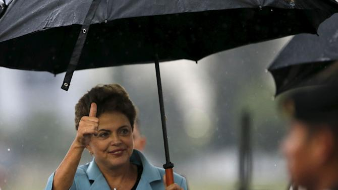 Brazilian President Dilma Rousseff gestures to the media after her arrival at the presidential hangar in Mexico City