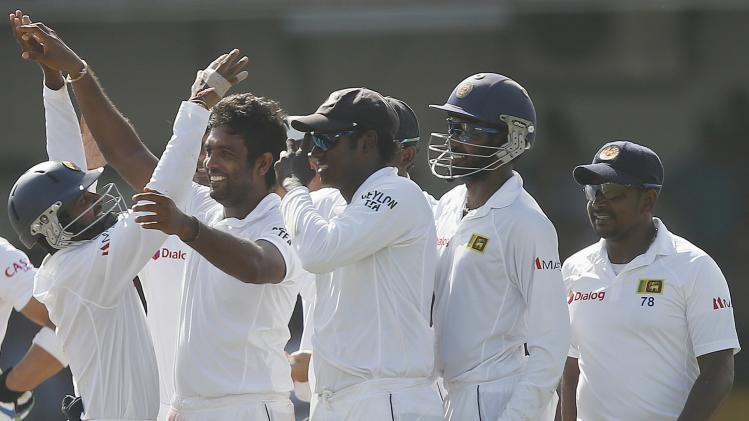 Sri Lanka's Perera celebrates with teammates after taking the wicket of South Africa's captain Amla during the fifth and final day of their second test cricket match in Colombo