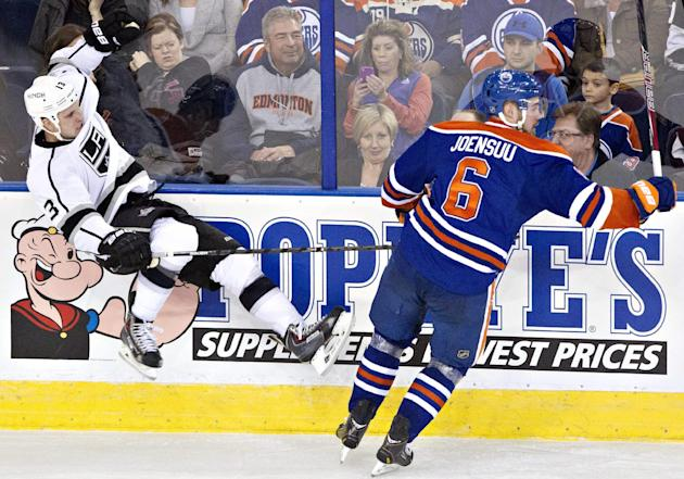 Los Angeles Kings Kyle Clifford (13) is checked by Edmonton Oilers Jesse Joensuu (6) during third period NHL hockey action in Edmonton, Alberta, on Sunday March 9, 2014