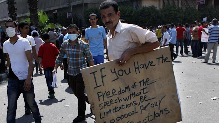 "An Egyptian protester holds a placard criticizing the western ""freedom of speech"" during clashes with riot police, unseen, near the U.S. embassy in Cairo, Egypt, Friday, Sept. 14, 2012, as part of widespread anger across the Muslim world about a film ridiculing Islam's Prophet Muhammad. (AP Photo/Nasser Nasser)"